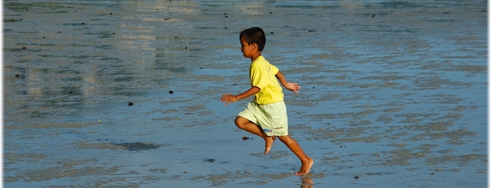 Boy not thinking of delaying gratification as he pushes himself to run on the beach in the heat.